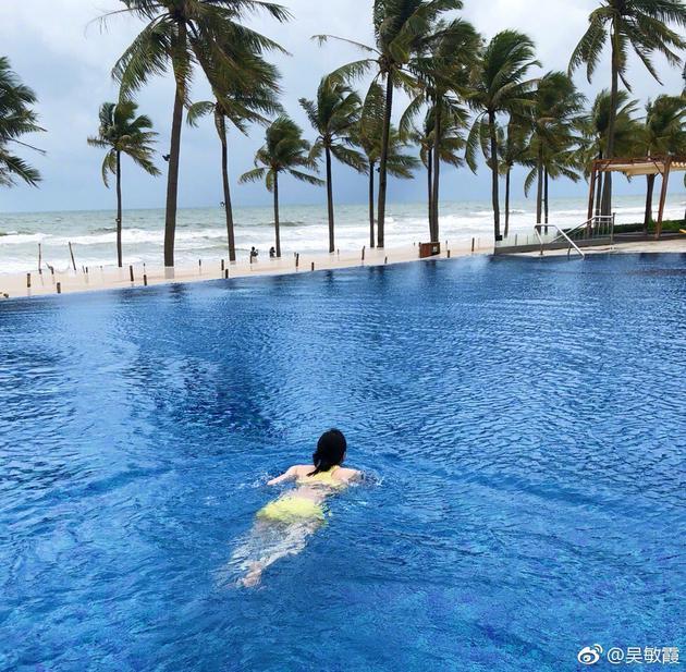 吴敏霞在微博晒出与老公海边度假的照片,孕肚明显