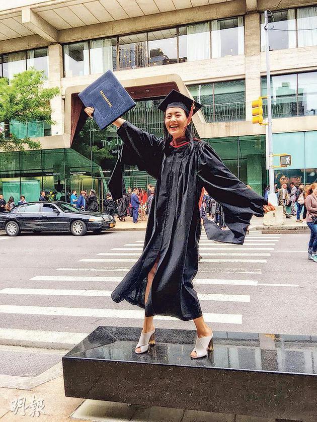 陈法拉穿着毕业袍、戴四方帽走到学校门前拍照。