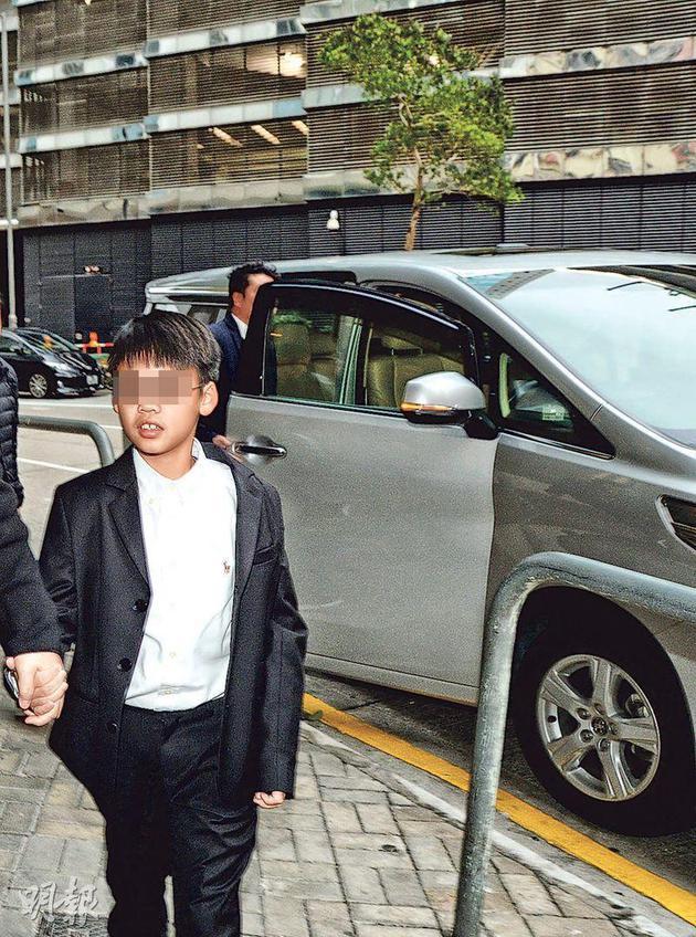 李嘉欣的7岁儿子许建彤,由助手陪伴下抵达灵堂。