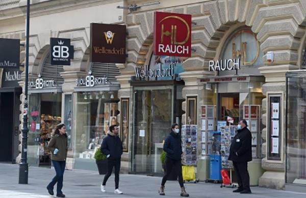 """奥地利4月14日起部分商店""""解禁"""",图为走过重新营业的商店的人们。新华社 图"""
