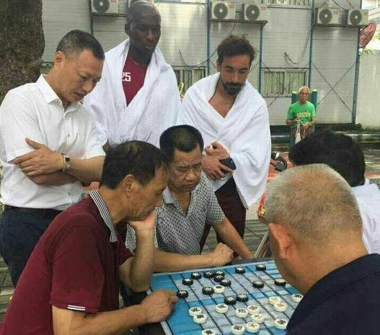 �神州幸福球员拉维奇、姆比亚看到路边大爷下象棋