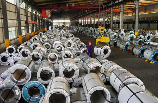 7月13日,河北省迁安市一家钢铁外贸企业的工人在生产车间内吊装彩涂板。