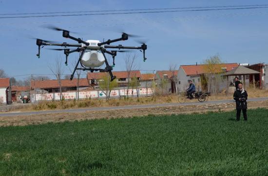 科技为农业生产带来变革。图为山东省高青县稻香农机合作社正在使用无人机喷洒农药。(乔金亮摄)