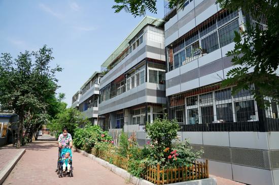 6月20日,市民在唐山市路南区已完成改造的新华南里社区内行走。