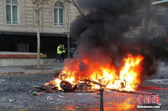 当地时间11月24日,巴黎香榭丽弃大街遭遇大周围示威活动。数以千计示威者荟萃在街上,竖立了不少路障,街道交通十足陷入瘫痪。图为示威者在香榭丽弃大街附近点燃的大火。中新社记者 李洋 摄