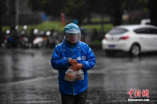 原料图:表卖幼哥冒雨送餐。中新社记者 刘冉阳 摄