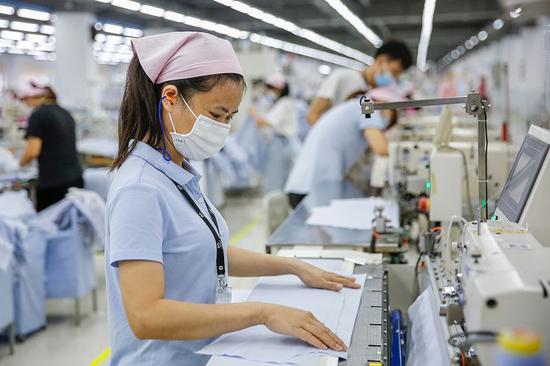 溢达集团佛山工厂的员工正在作业。供图/溢达集团
