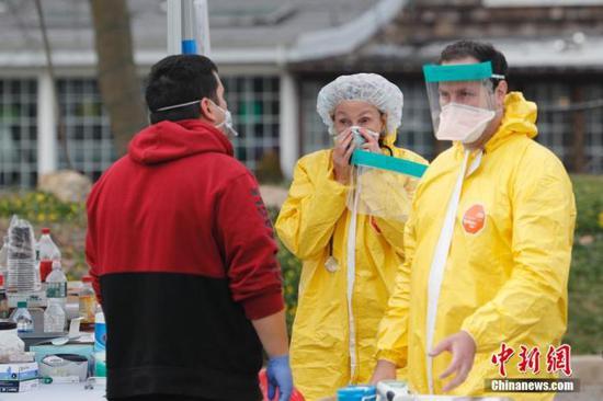 當地時間3月18日,美國紐約州拿騷縣的一處醫療中心戶外停車場正在進行免下車新冠病毒檢測,醫務人員工作交流。 中新社記者廖攀攝