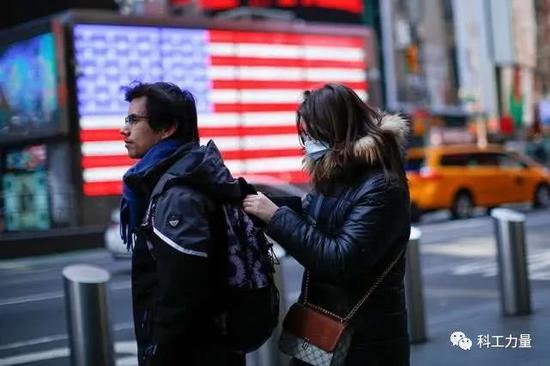 3月8日,在美国纽约时报广场,一名女子戴着口罩。图/新华社