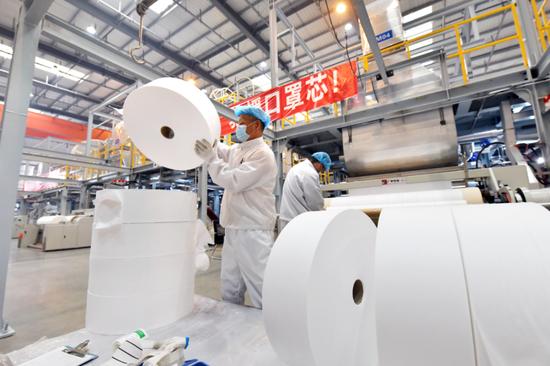 4月20日,工人在中石化仪征化纤生产车间里整理熔喷布。