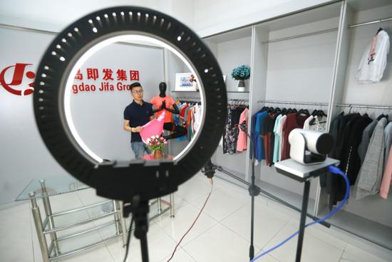 6月15日,山东省青岛市即墨区即发集团的营销人员通过广交会直播平台推介出口到海外市场的服装产品。