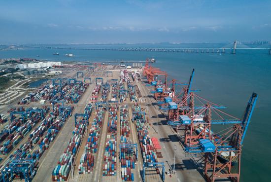 7月15日,在福建泉州最主要的现代集装箱港石狮石湖港,大型机械在吊装集装箱。