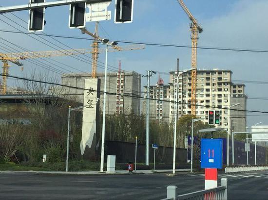 项目北侧已拆除防护网的高层公寓