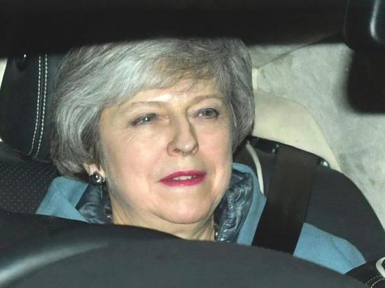 """2月14日,在英国伦敦,英国首相特雷莎⋅梅乘车离开议会。英国议会下院14日投票否决了首相特雷莎⋅梅提出的一项动议,该动议要求议会支持政府与欧盟谈判修改""""脱欧""""协议。(新华/美联)"""