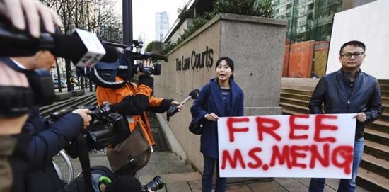 当地时间10日,在法庭外貌,有华人群多举首标语,请求开释孟晚舟女士