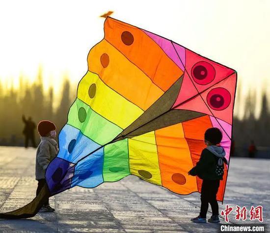 资料图:3月22日,敦煌市民在敦煌鸣沙山下党河大桥附近的空地上放风筝。 王斌银 摄