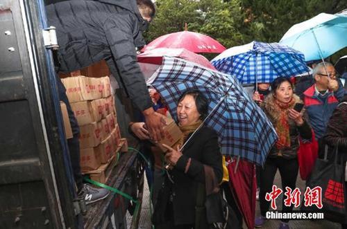 资料图:上海百名居民感�X在雨中排成一条长龙,领取刚到货的秭归脐橙。拼多多供图