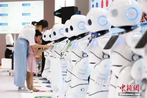 图为小朋友与机器人互动。?中新社记者 富田 摄