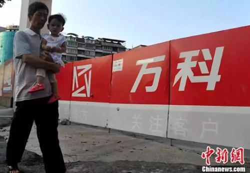 资料图:福州民众从万科楼盘工地旁经过。中新社记者 张斌 摄