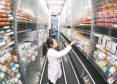图为江苏省连云港市第一人民医院智慧药房,工作人员正在查看智能药物存储管理分发系统运行情况。   耿玉和摄(人民视觉)