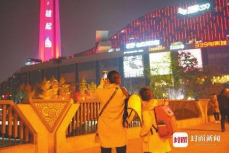 2019年12月9日,成都天府熊猫塔为电竞战队助威的灯火引得市民停步拍照。
