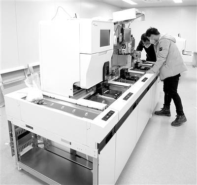 图为2月5日,技术人员在建设中的武汉雷神山医院内调试尿液分析仪。新华社记者 王毓国 摄