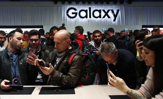 2月25日,在西班牙巴塞罗那,人们体验新款三星盖乐世S9手机。 (新华社)