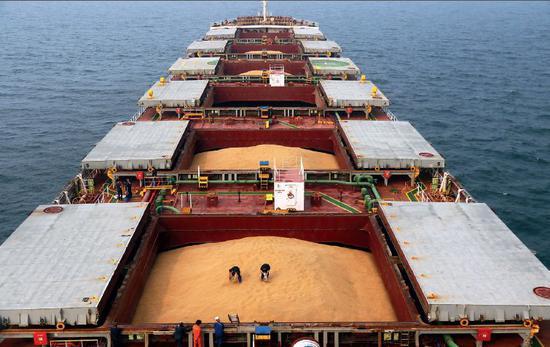 (资料图片)山东烟台港,检验检疫人员对轮船上的进口大豆进行取样和感官检疫。图/中新
