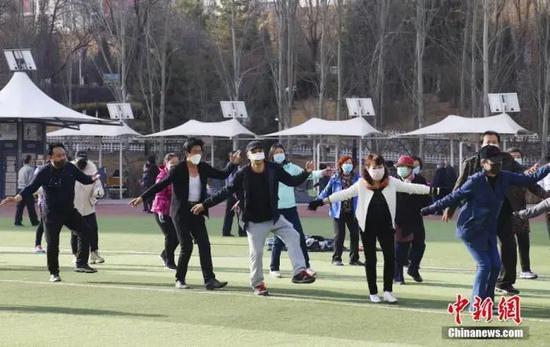 资料图:3月20日,西宁市户外体育场所已全部开放,市民在体育场上跳起锅庄。中新社记者 马铭言 摄