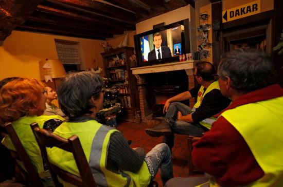 """""""黄背心""""示威者不雅旁观马克龙电视说话。"""