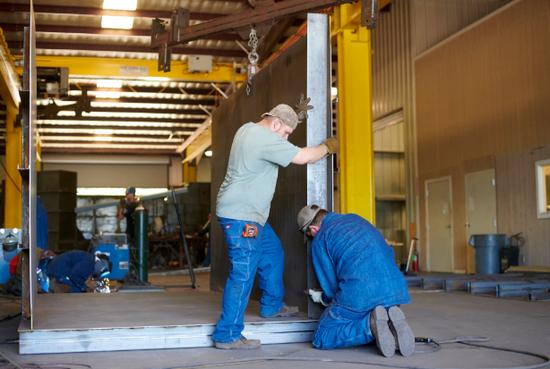 在德克萨斯州默奇森的Rising S Co.制造工厂,工人们在一个地下钢掩体的框架上工作。