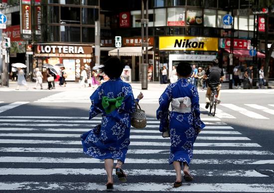 原料图片:2018年7月,日本东京,两名身着和服的女子通过购物街区的人走横道。REUTERS/Kim Kyung-Hoon