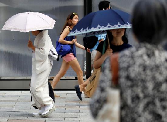 资料图片:2018年7月23日,日本东京,街头步履匆匆的女子。REUTERS/Issei Kato