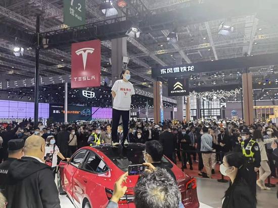 上海车展现特斯拉车主站车顶维权 疑似被保安强行拖离现场