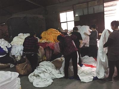 3月17日上午,南沟村的洗涤厂,工人在地上分拣布草。