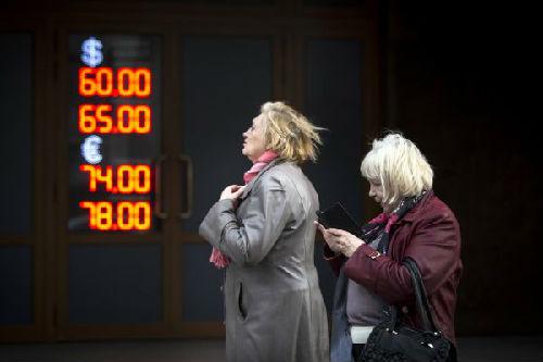 4月10日,在俄罗斯首都莫斯科,行人从一处外汇兑换点经过。(新华社/美联)