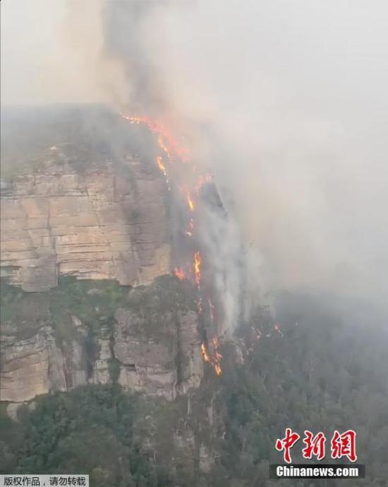 """近日,澳大利亚野火蔓延进悉尼野外的世界遗产蓝山国家公园,园内山峰的悬崖上形成""""火瀑布""""。现在,该公园已不准游客入园,并停息一切运动。"""