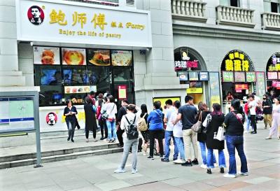 """22日中午,江汉路地铁站D出口附近挂着""""鲍师傅""""招牌的糕点店门前,十几个人正在排队"""