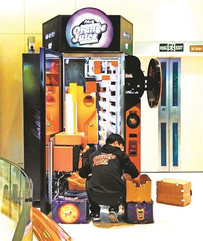"""在朝阳区某商场,""""天使之橙""""的工作人员正在向机器里添加橙子摄影/本报记者张鑫"""