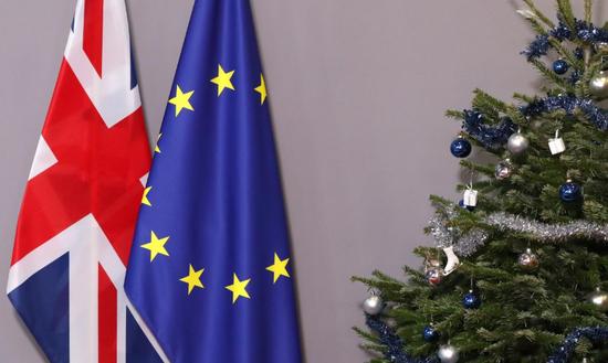 2018年12月11日,比利时布鲁塞尔,欧盟委员会总部内一颗圣诞树旁摆放的欧盟和英国旗帜。REUTERS/Yves Herman