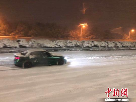 从南京机场前往市区的机场高速路面出现积雪。雪夜里,接送乘客的车辆缓慢行驶。 朱晓颖 摄
