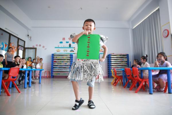 河北一幼儿园小朋友展示用废旧物品制作的服装。