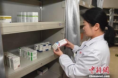 资料图:医生正在为病人取药。中新社记者 杨华峰 摄