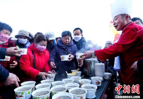 资料图:甘肃张掖厨师在给市民盛免费腊八粥。王将