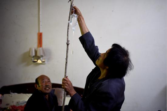 卢氏县五里川镇毛坪的尘肺农民兄弟王福山正插着24小时都不能停的制氧机,支着树枝打着消炎点滴