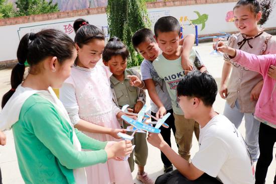 浙江大学志愿者和学生一起制作航模