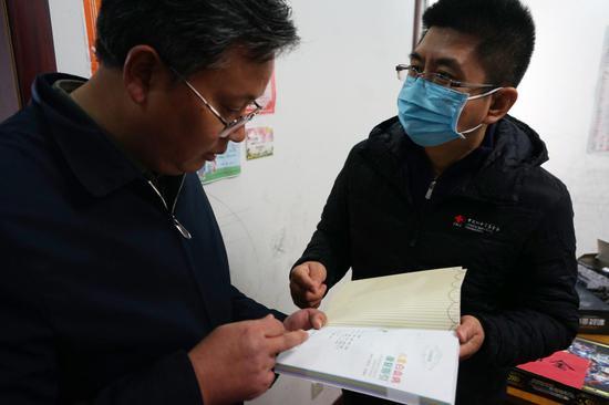 中国红基会的工作人员向小峰的爸爸赠送了《儿童白血病康复指引》
