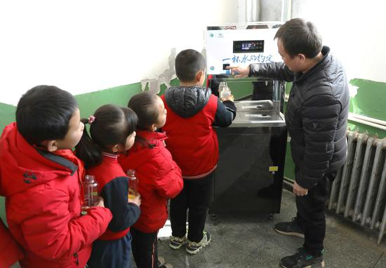 """阁楼小学周校长与孩子们体验由""""绿动未来""""平台捐赠的净水设备"""