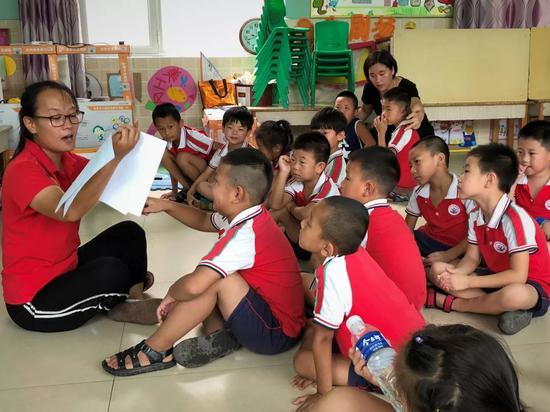 """阳光幼儿教师在引导孩子们思考""""什么样的浇水工具能帮助我们更好地浇地""""。"""