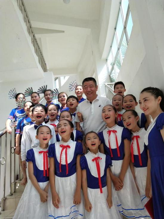 第五届童声飞扬音乐会上成美理事长蒋先生在后台了解孩子们的音乐学习情况